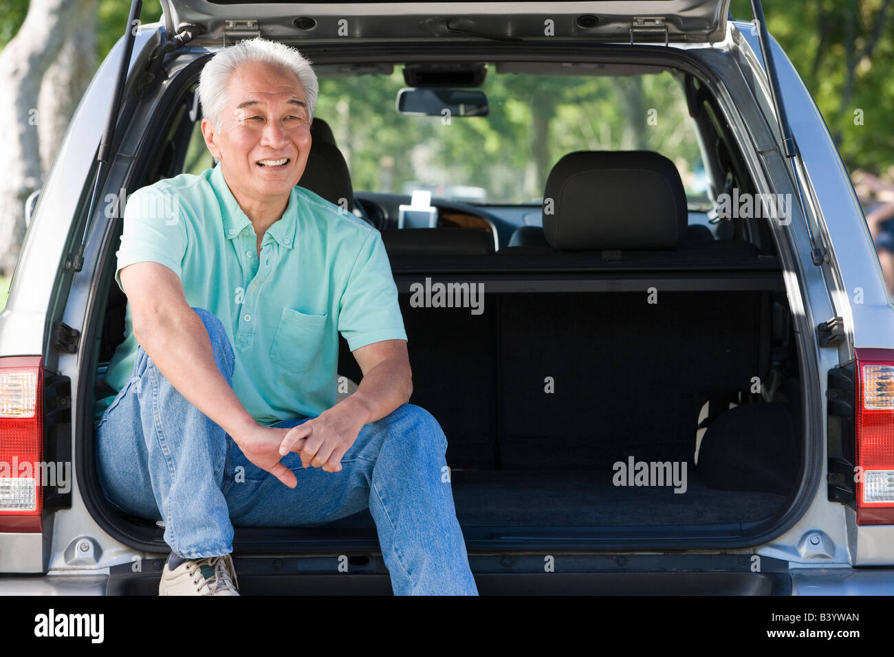Man sitting in back of van smiling - Stock Image