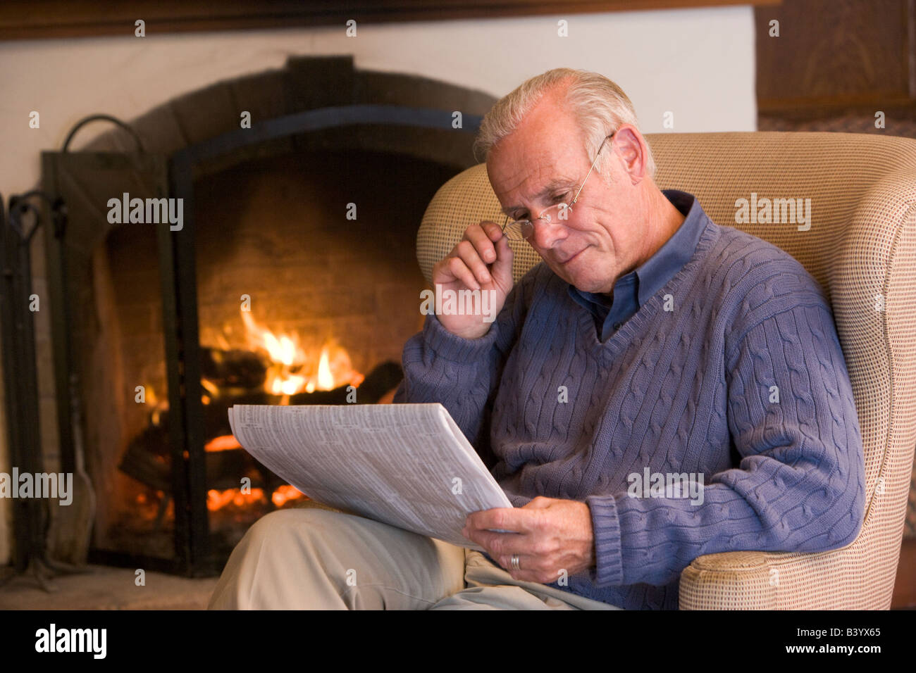 Man sitting in living room by fireplace with newspaper Stock Photo