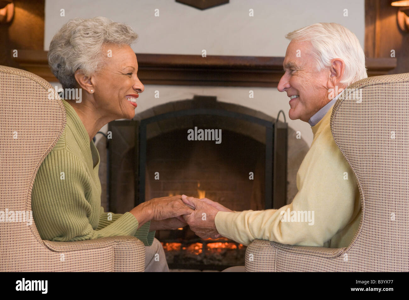 Couple sitting in living room by fireplace holding hands and smiling - Stock Image