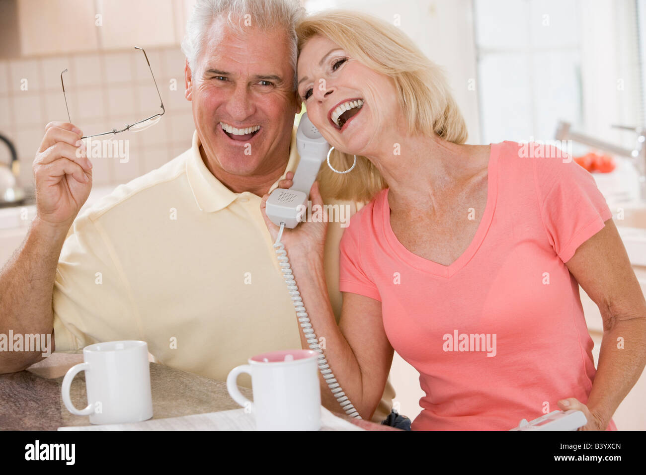 Couple in kitchen using telephone together and laughing - Stock Image