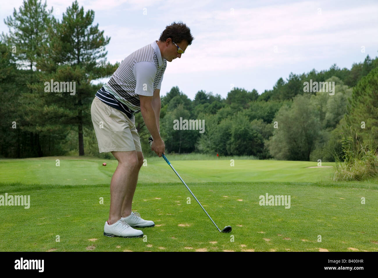 Golfer addressing the ball as he is about to tee off with an iron on a short par three - Stock Image