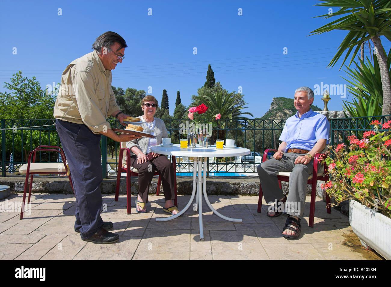 Proprietor Andreas serving breakfast Paleo Inn Corfu - Stock Image