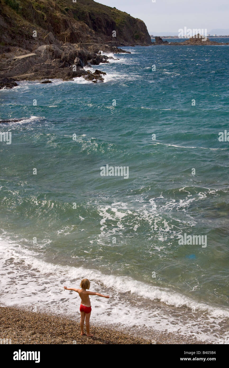 A child is standing alone on the beach at Collioure / Southern France - Stock Image