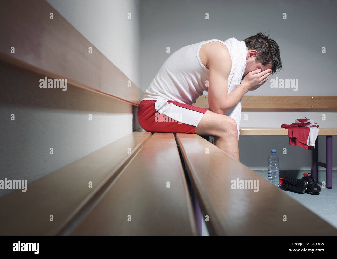 Exhausted soccer player sitting in changing room - Stock Image