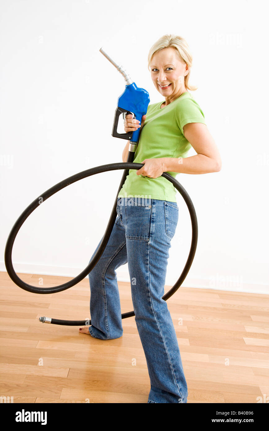Portrait of adult blonde woman holding gas nozzle like a gunslinger - Stock Image