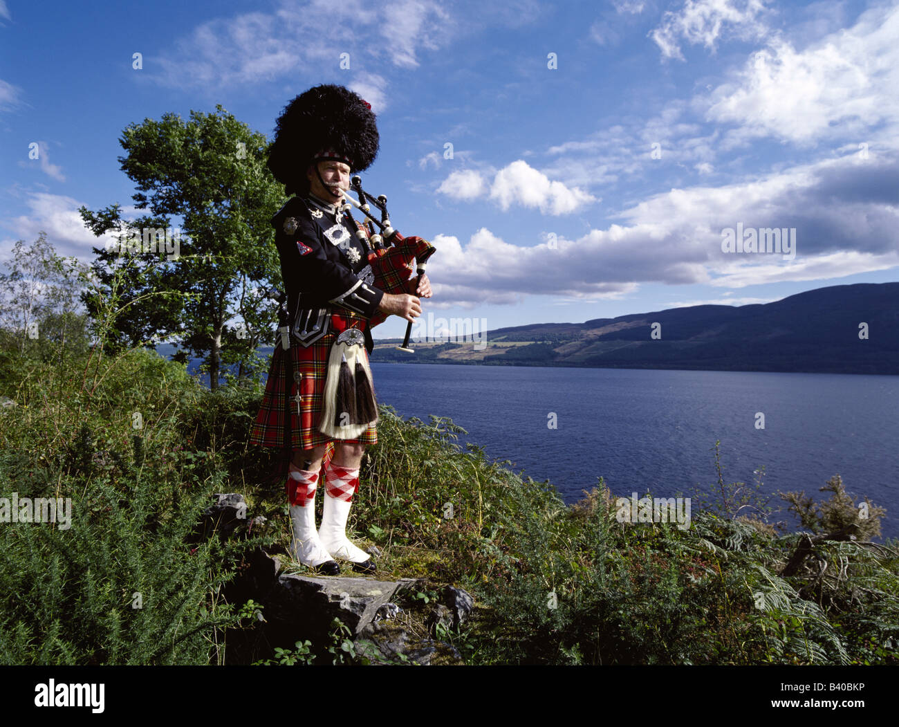 dh  LOCH NESS SCOTLAND Scottish piper bagpipes tartan kilt uniform piping bagpiper in highlands traditional highland dress bag pipes man Stock Photo