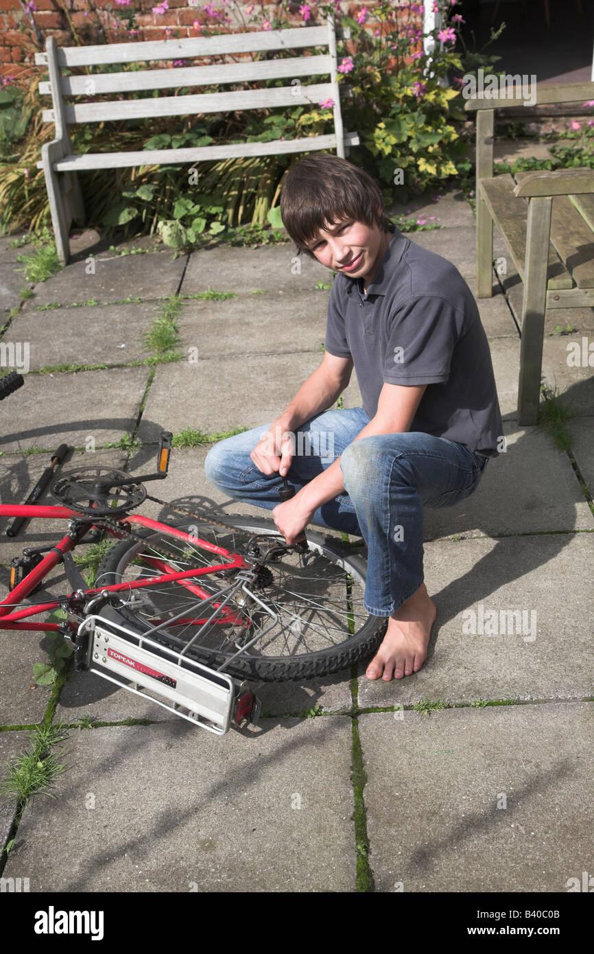 Teenage boy repairing bicycle puncture Stock Photo