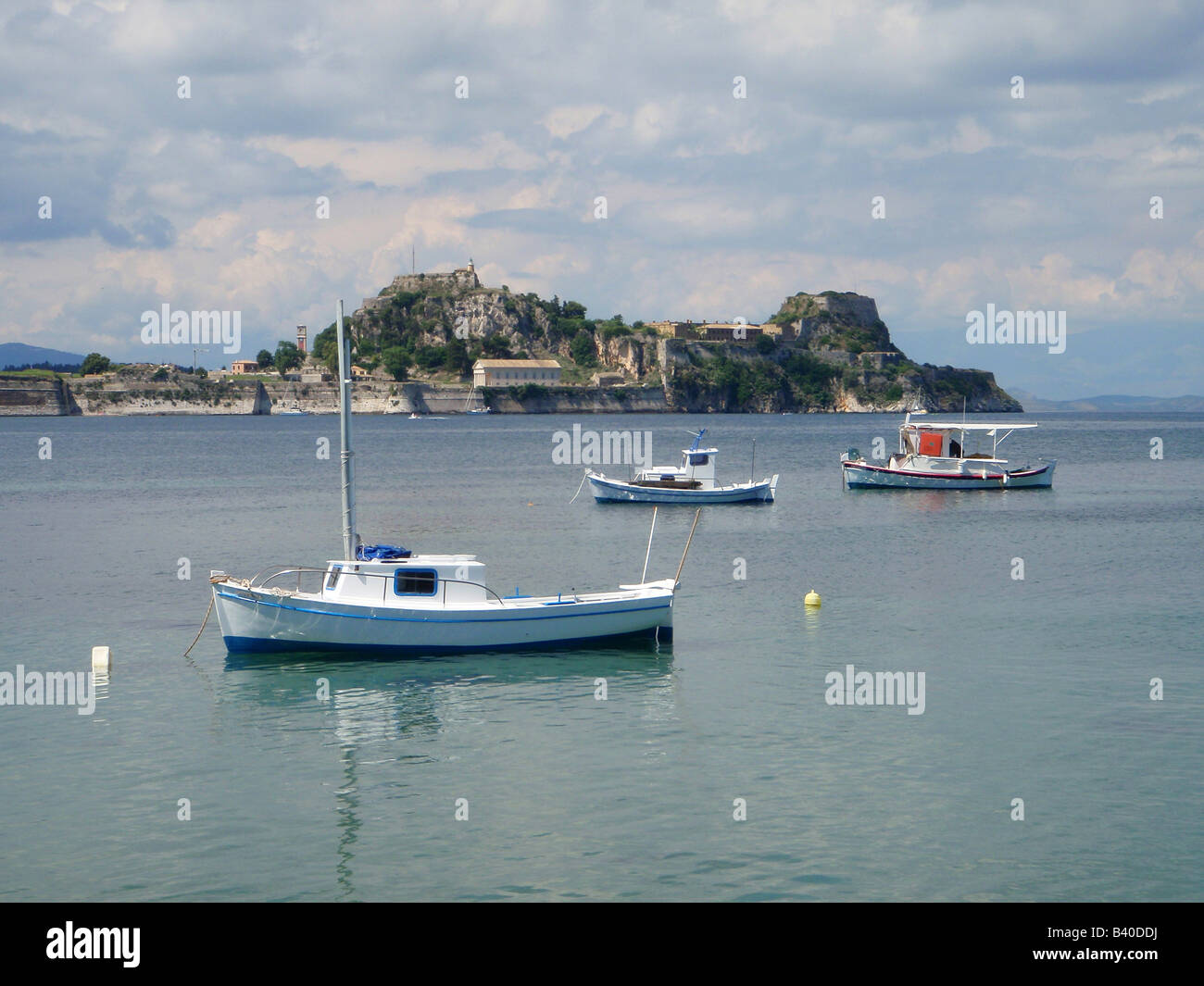 Fishing boats in a quiet bay near Garitsa, overlooking the Old Fort. Corfu, Greece. - Stock Image