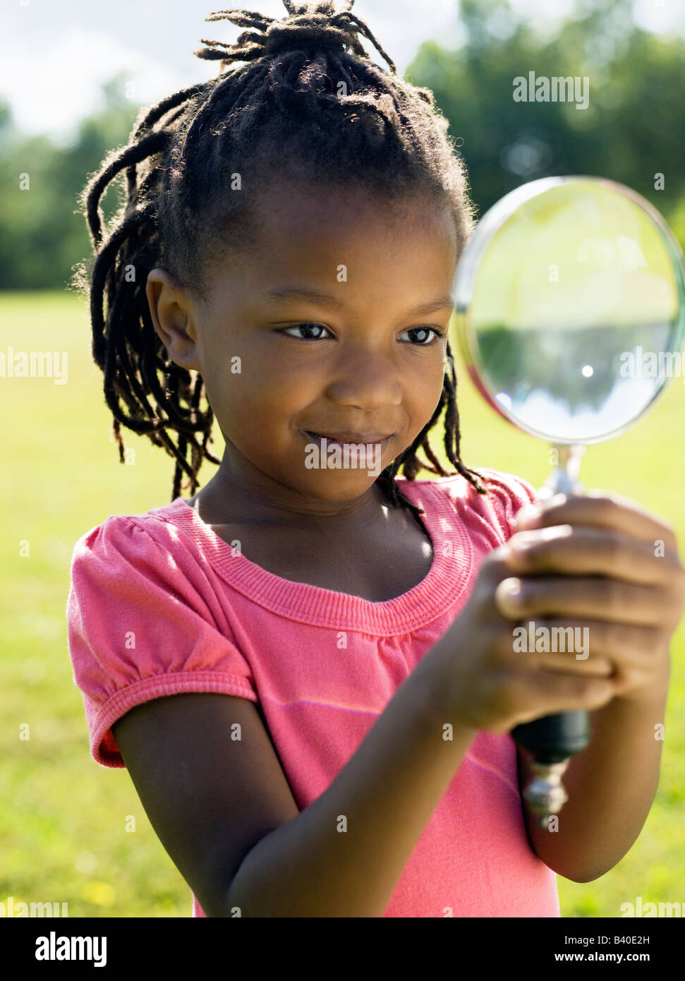 Young African American girl looking through magnifying glass Chicago - Stock Image