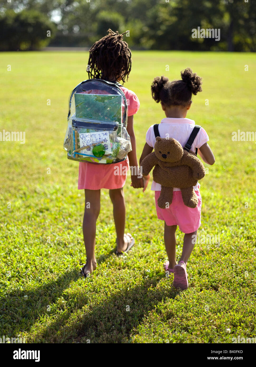 Two young girls carrying backpacks walking to school in Chicago park - Stock Image