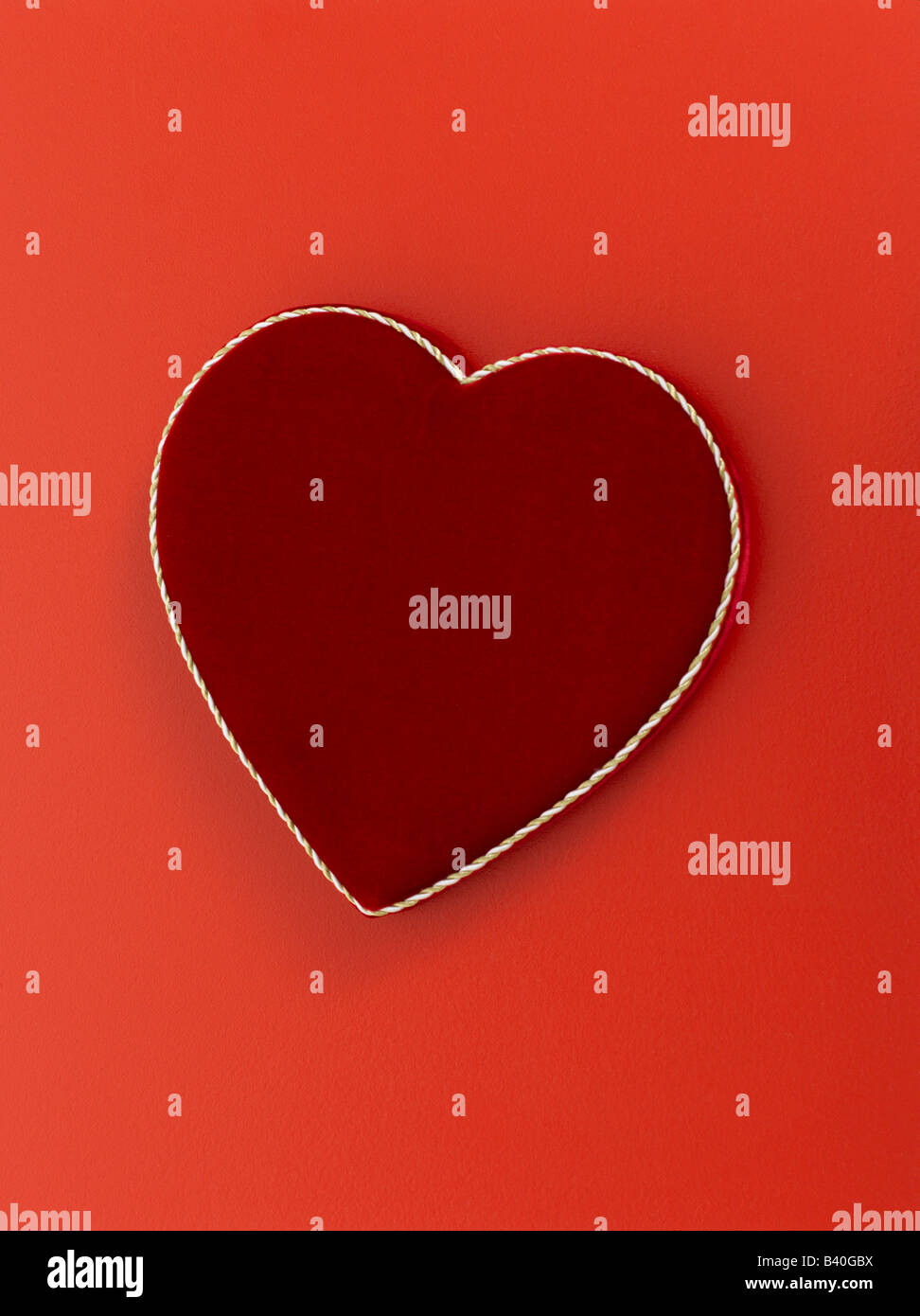 Heart shaped valentines day chocolate box on red background - Stock Image
