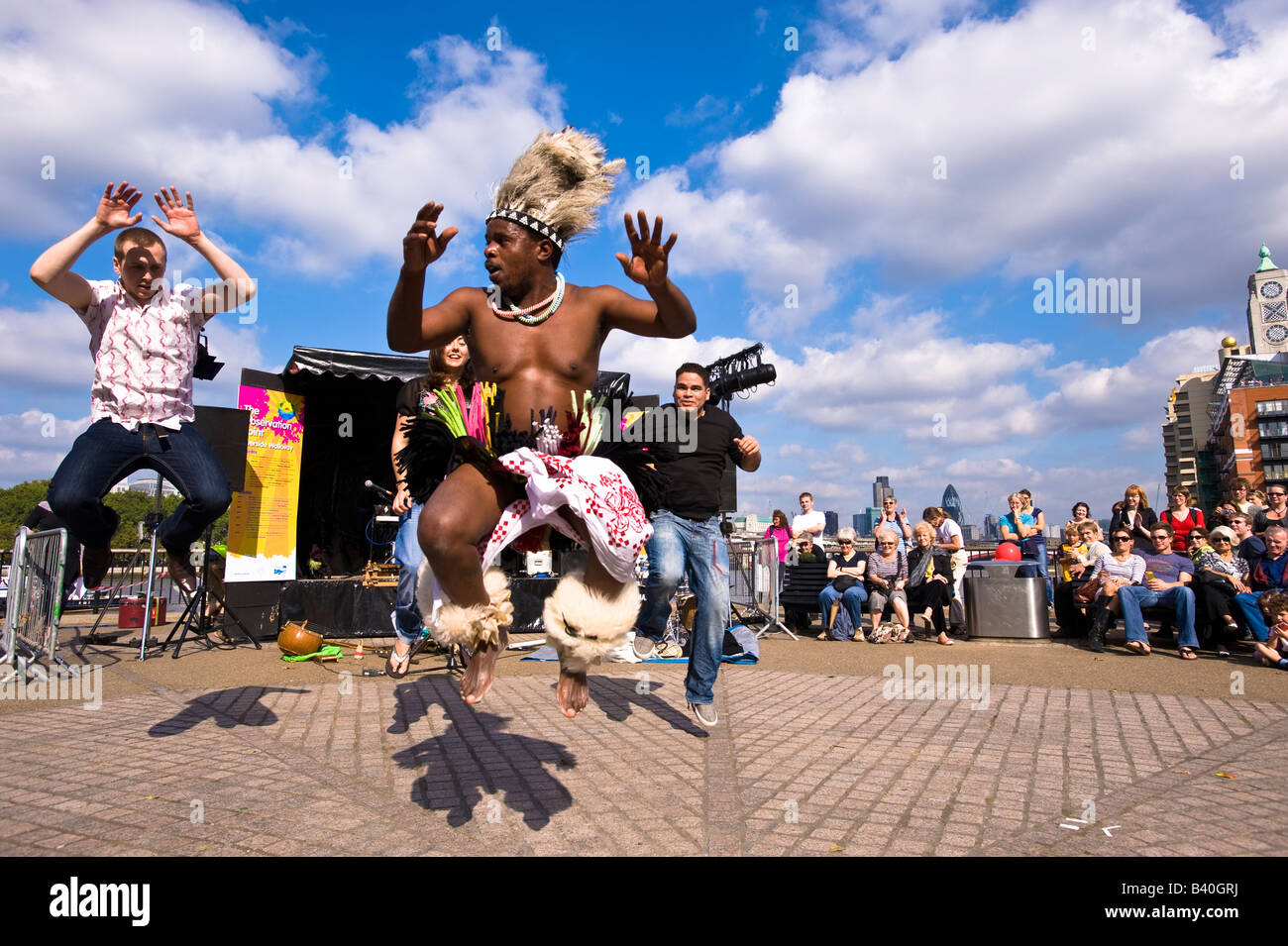 African street performer entertaining tourists and passersby during Thames Festival Southbank SE1 London United - Stock Image