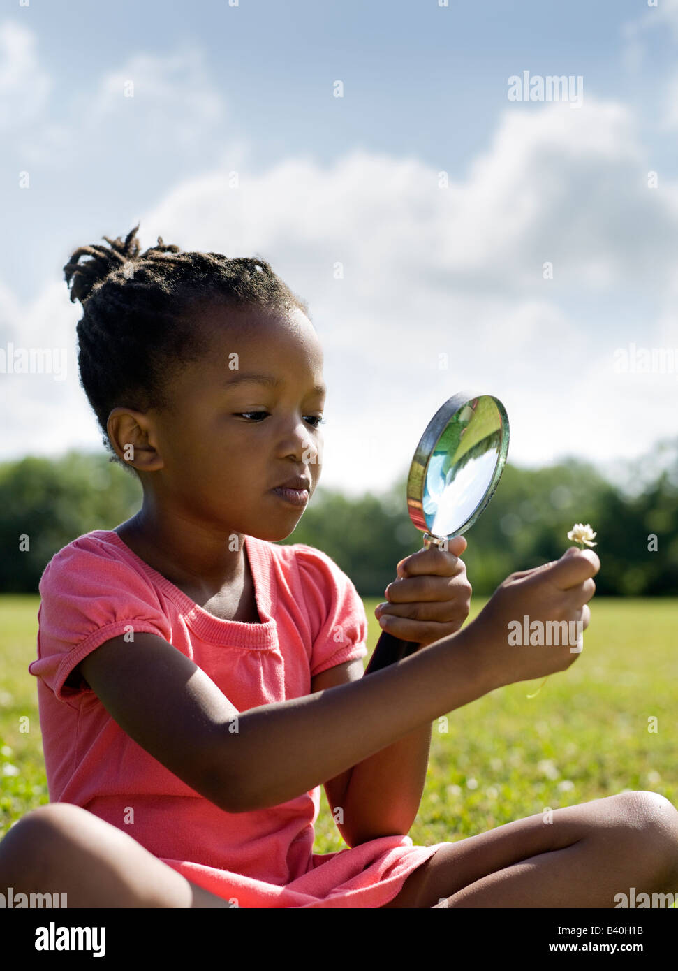 Young African American girl looking at flower with magnifying glass Chicago - Stock Image