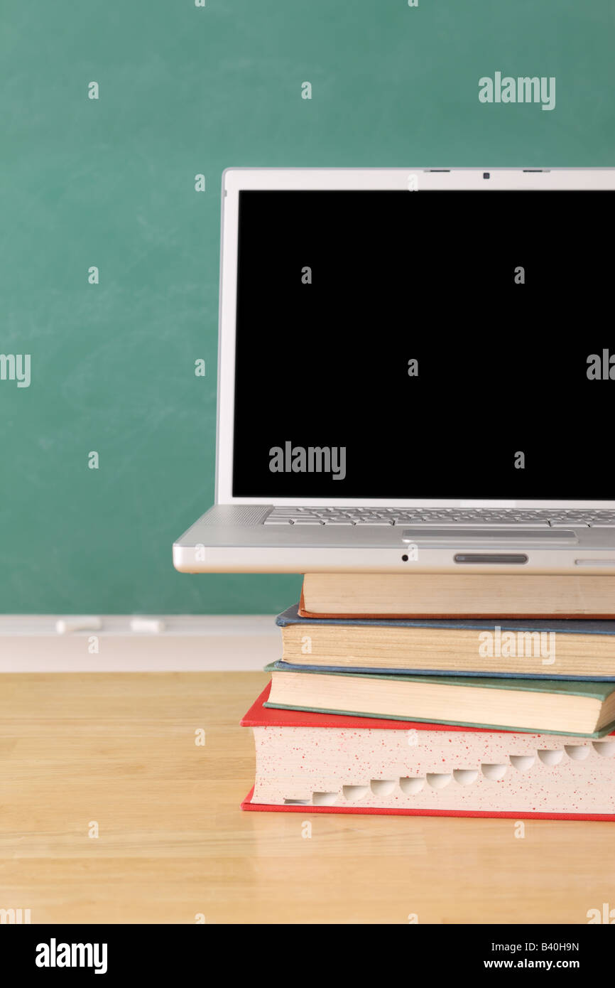 School education still life with laptop on stack of books - Stock Image