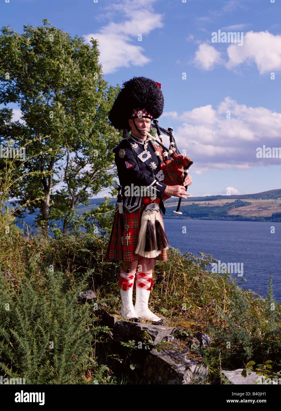 dh Scottish piper LOCH NESS INVERNESSSHIRE Bagpipes tartan kilt uniform lochside scotland bagpiper scotsman bagpipe - Stock Image