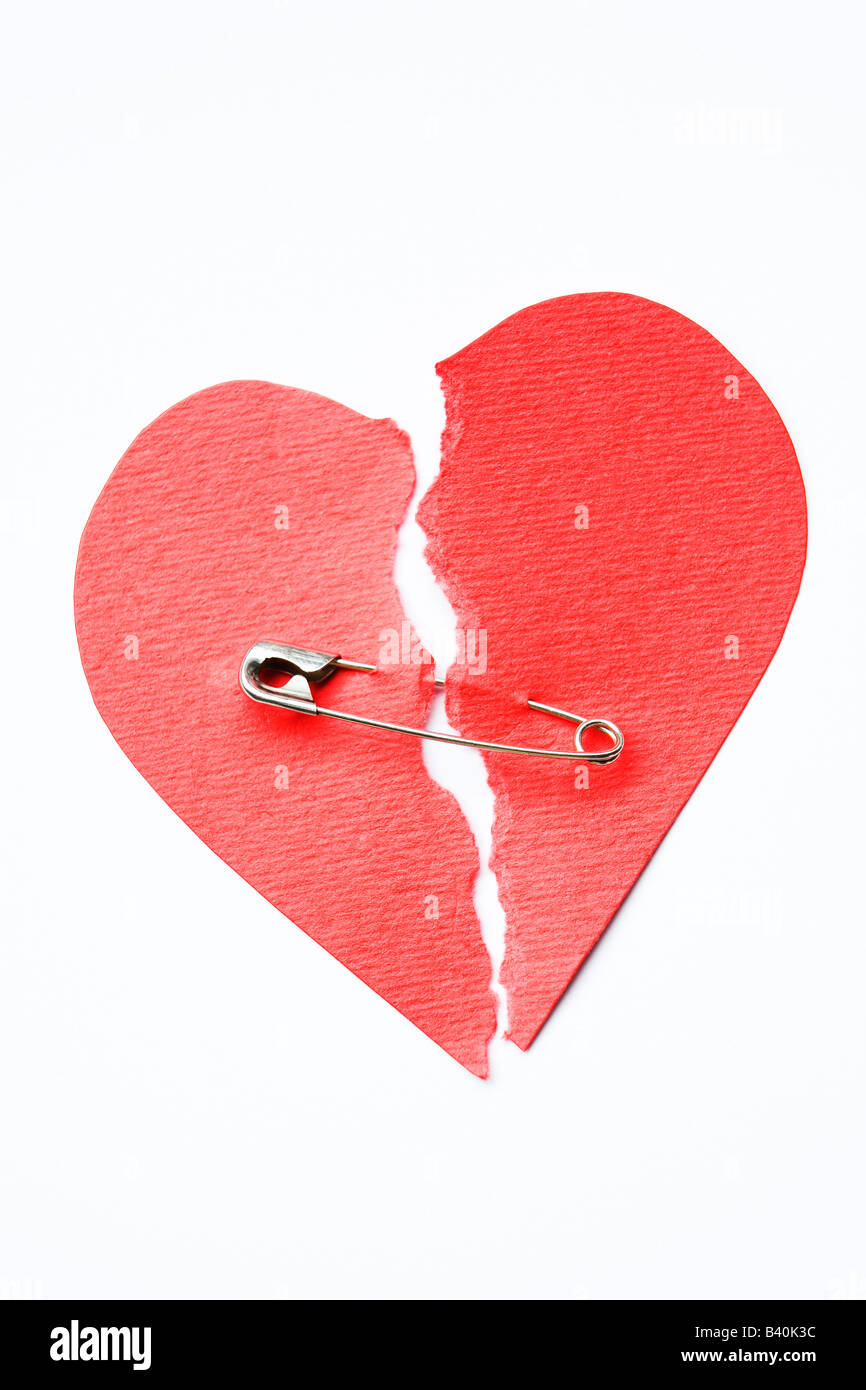 Broken heart joined with safety pin - Stock Image