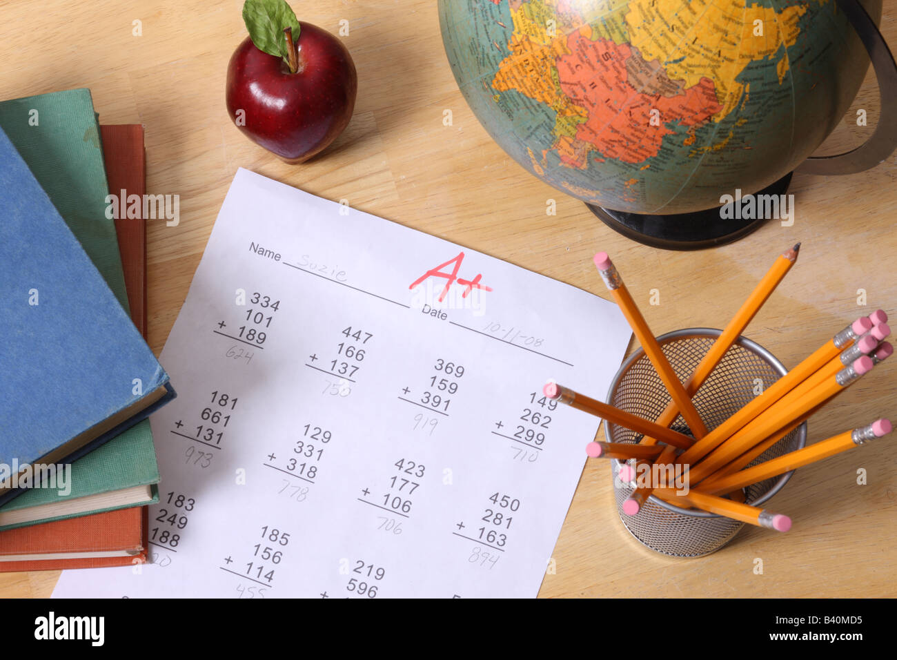 School education still life with books globe apple pencils and a paper with A grade - Stock Image