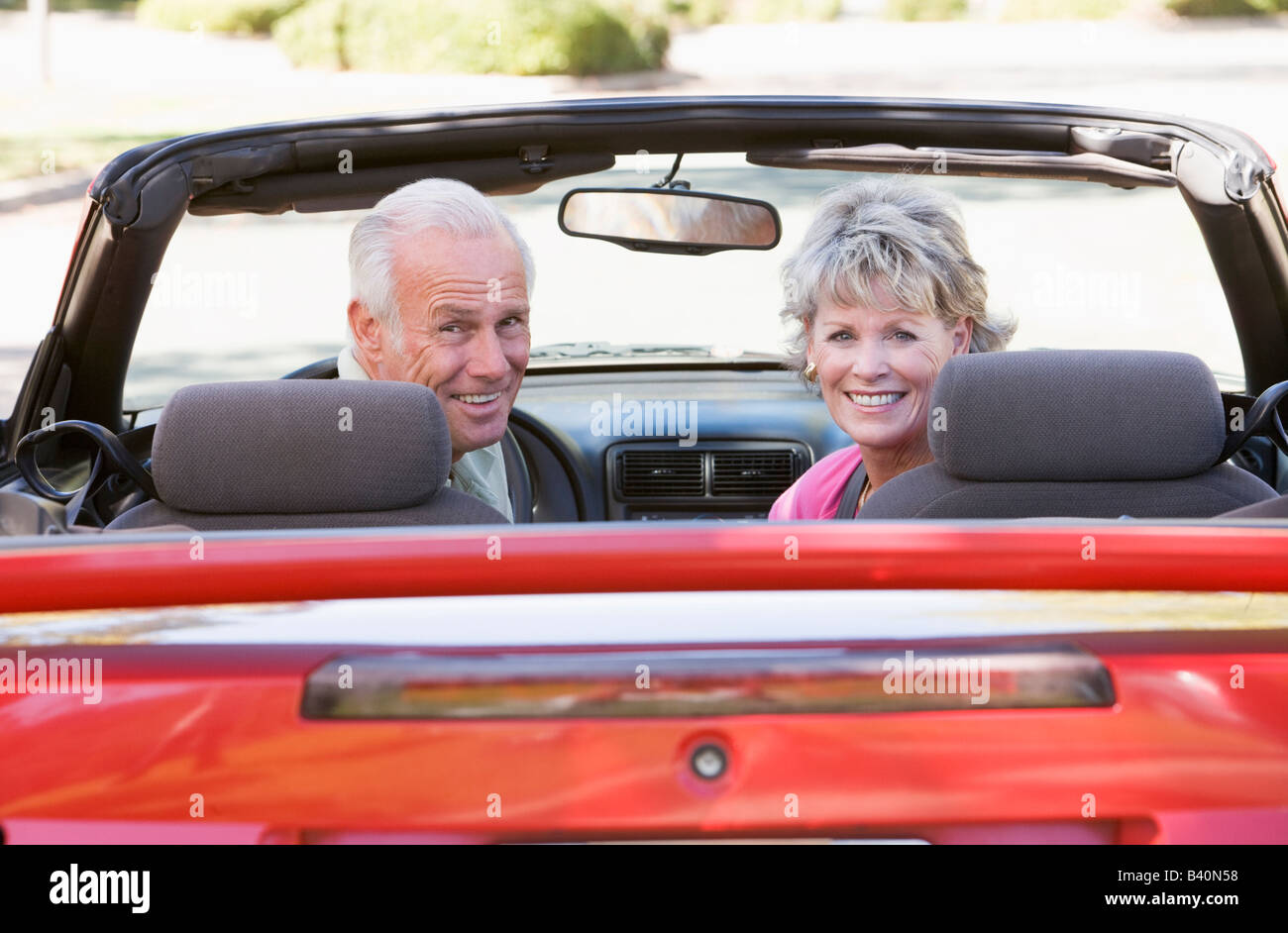 Couple in convertible car smiling - Stock Image