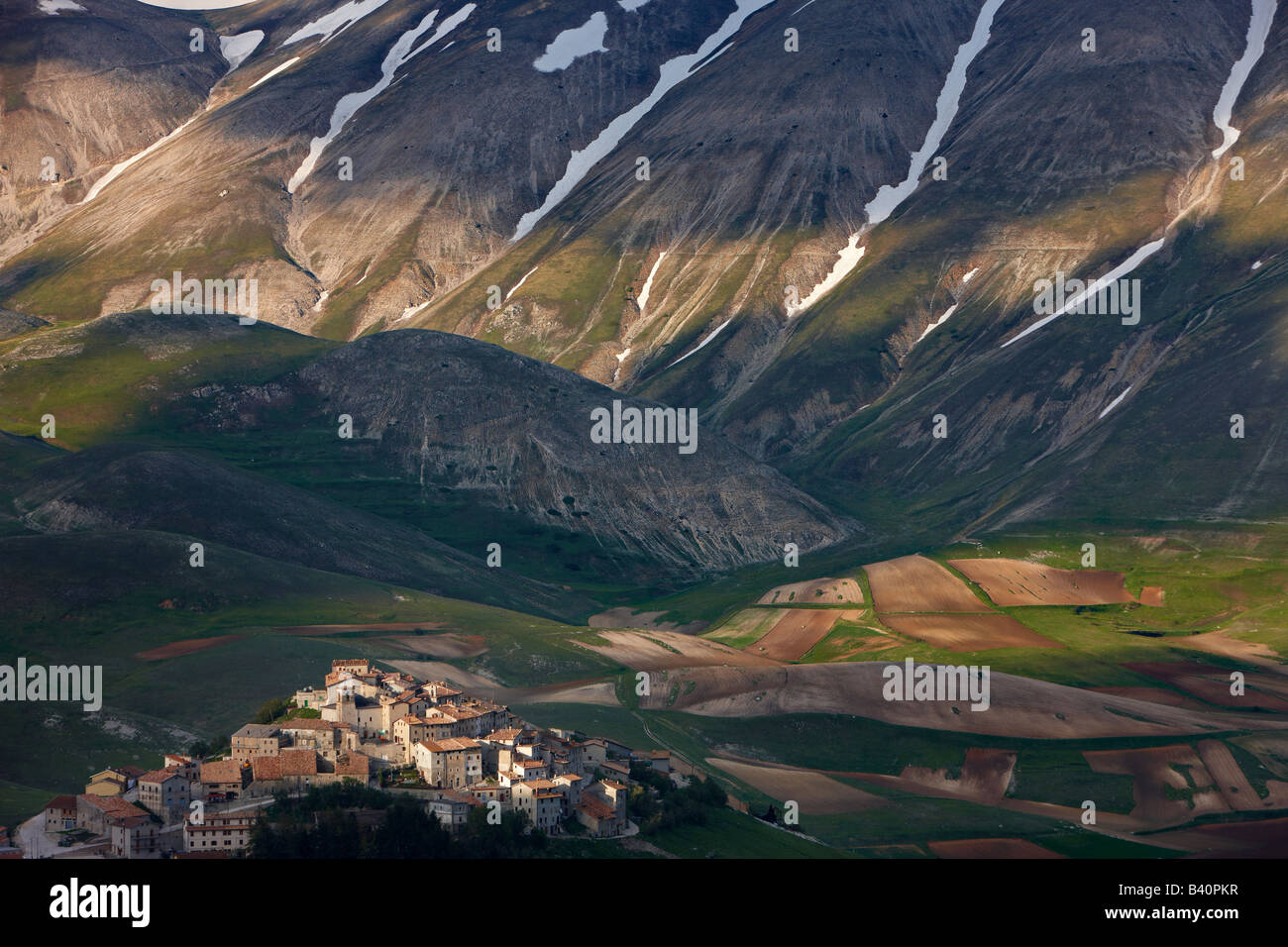 the village of Castelluccio perched above the Piano Grande with the mountains of Monti Sibillini National Park, - Stock Image