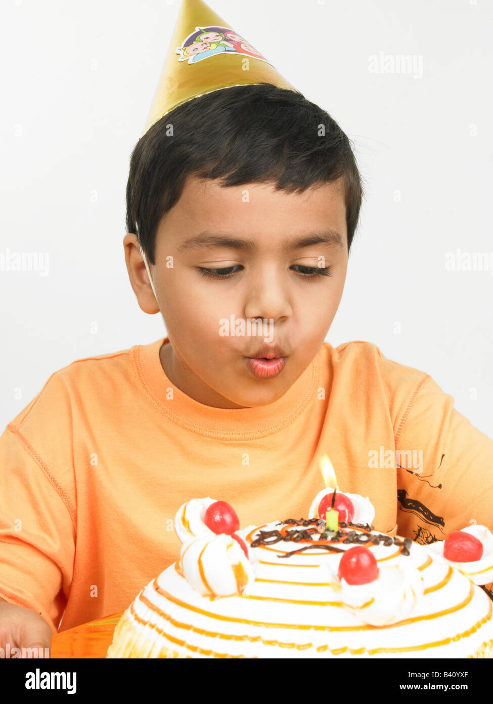 Asian Boy Of Indian Origin Blowing The Candle On His Birthday Cake