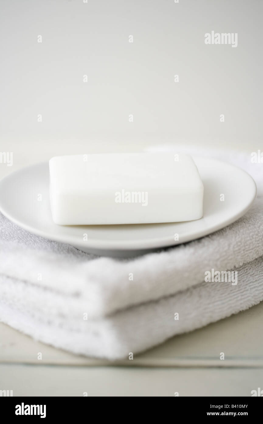 Cake of soap on a disc on a stack of towels - Stock Image