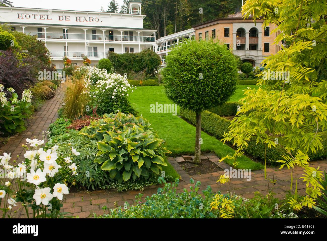 USA, WA, San Juan Island.  Roche Harbor historic Hotel de Haro and gardens with new Quarryman Hall addition - Stock Image