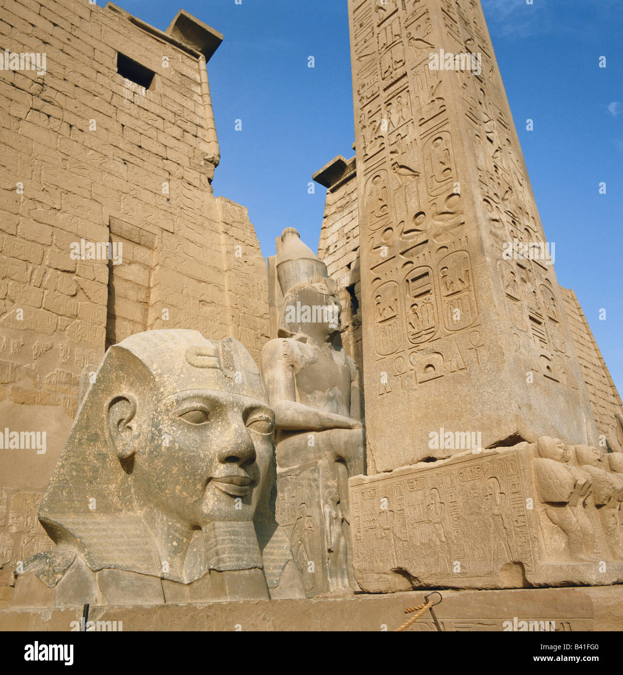 Luxor colossal head statue and obelisk at the Temple of Luxor, Egypt, Nile Valley, North Africa Stock Photo