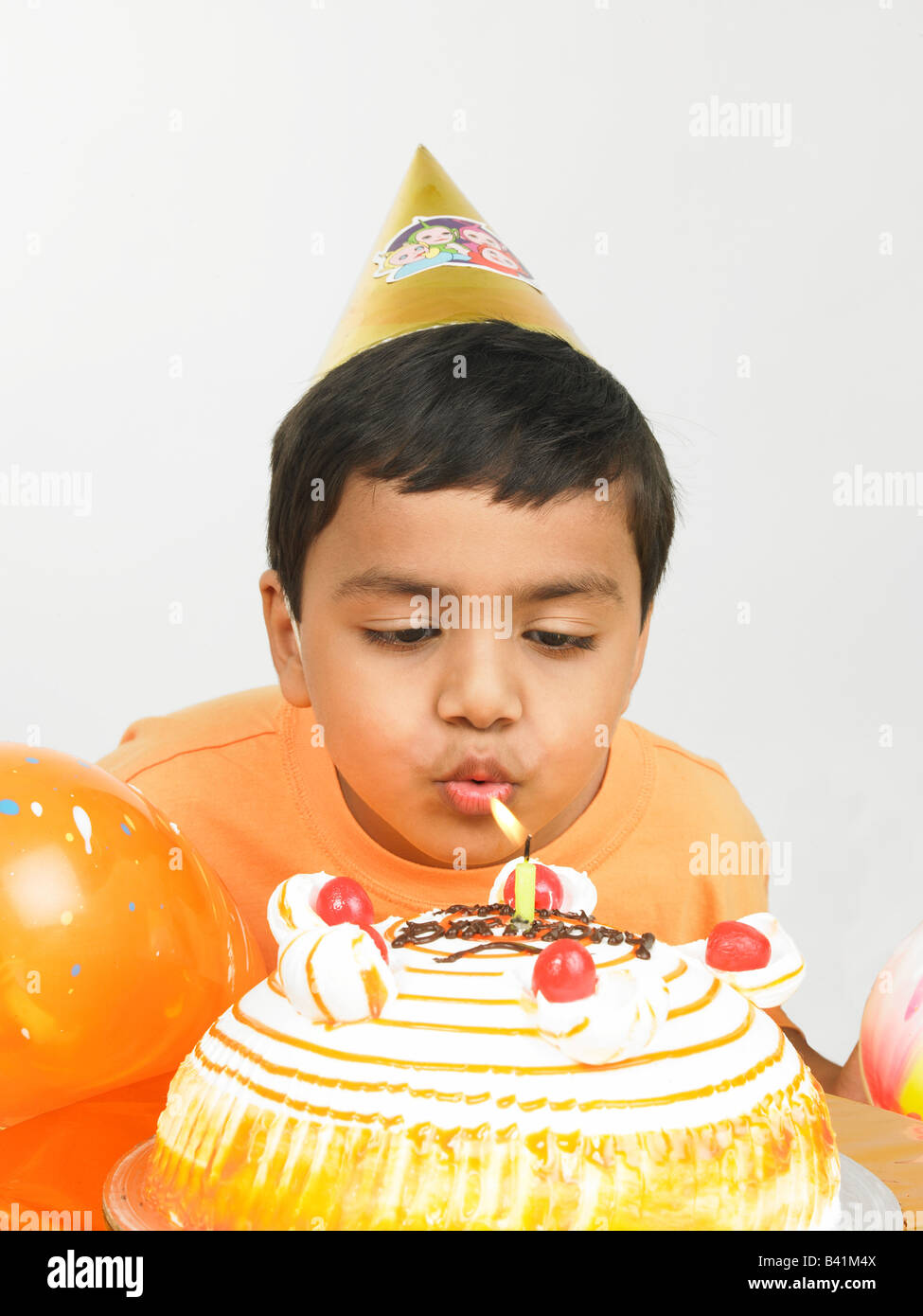 asian kid of indian origin blowing the candle of his birthday cake - Stock Image