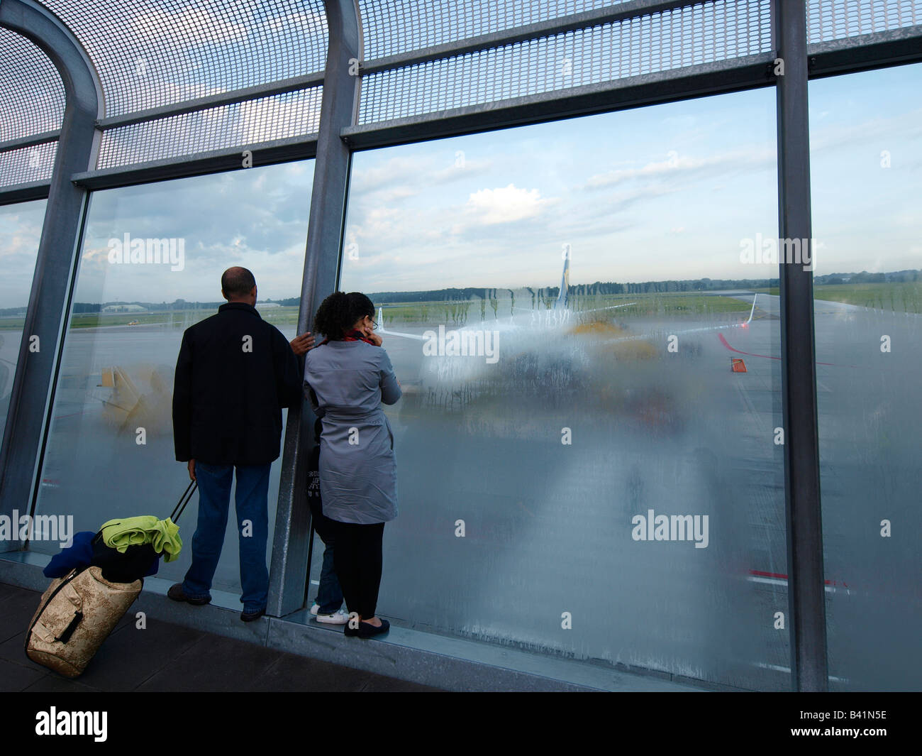Family looking at the Ryanair aeroplane they will be taking off with later Eindhoven airport NL - Stock Image