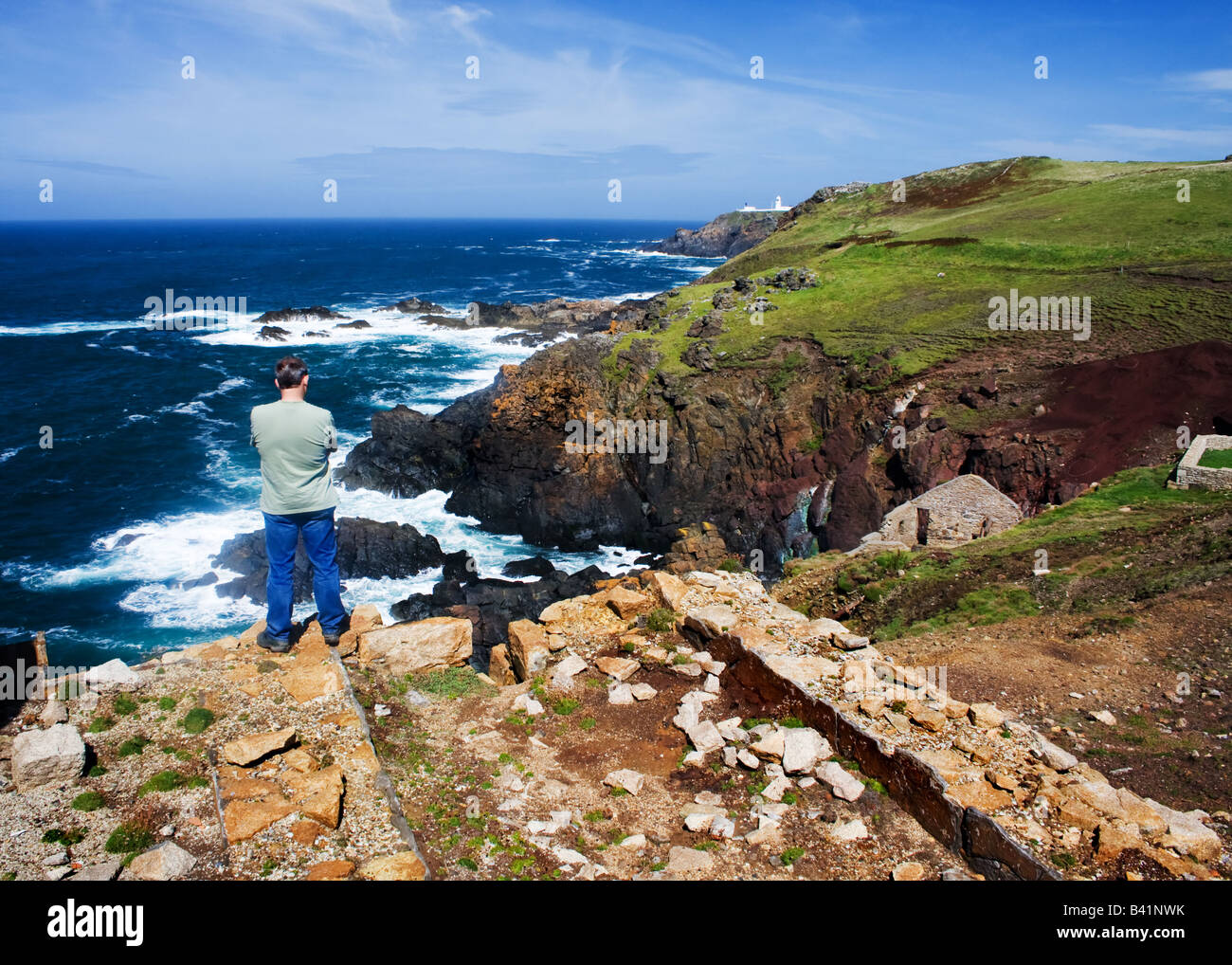 Man looking out to sea at Levant tin mine on the Cornish coast. - Stock Image