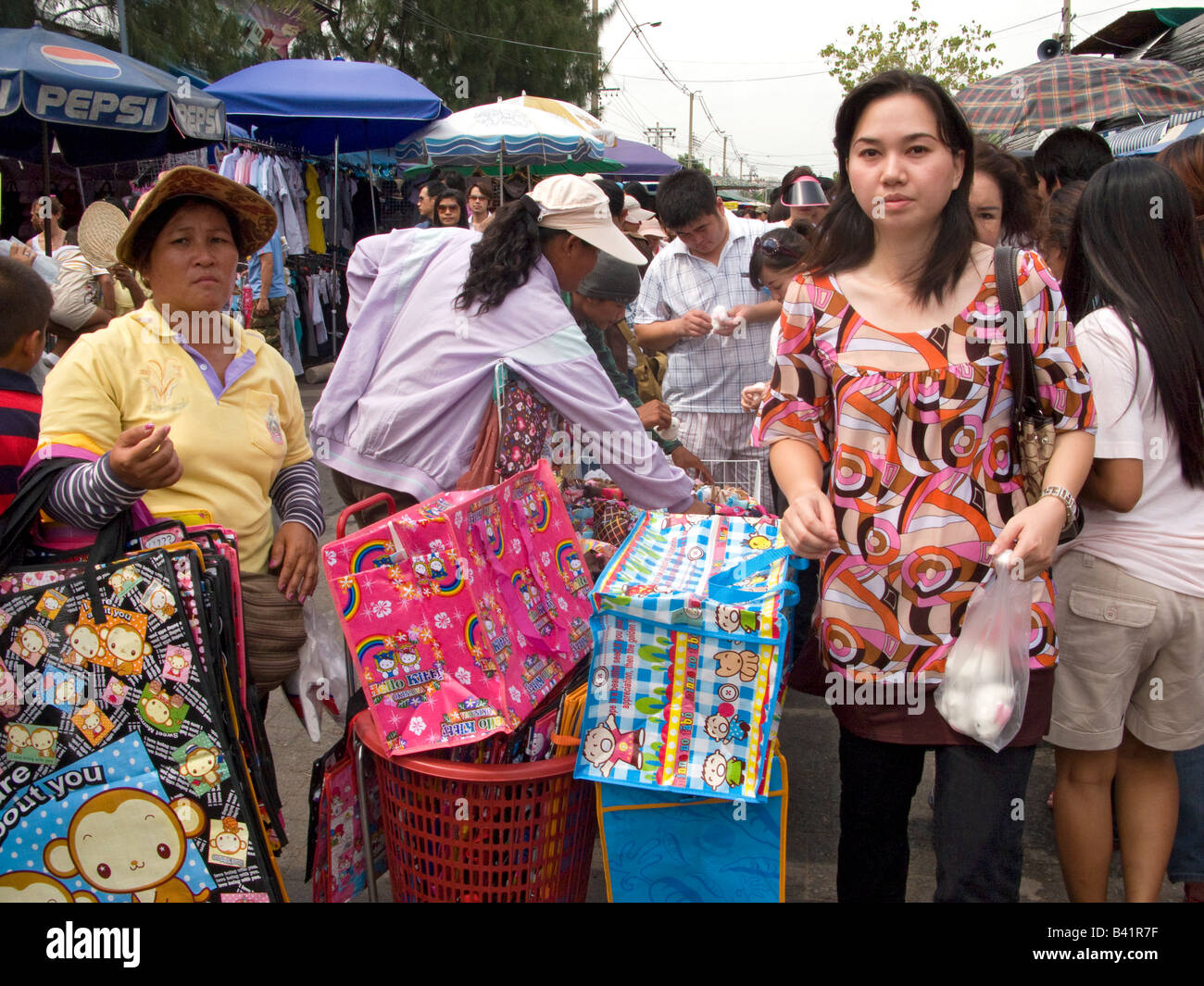 Thai woman walking through Chatuchak market, Thailand - Stock Image
