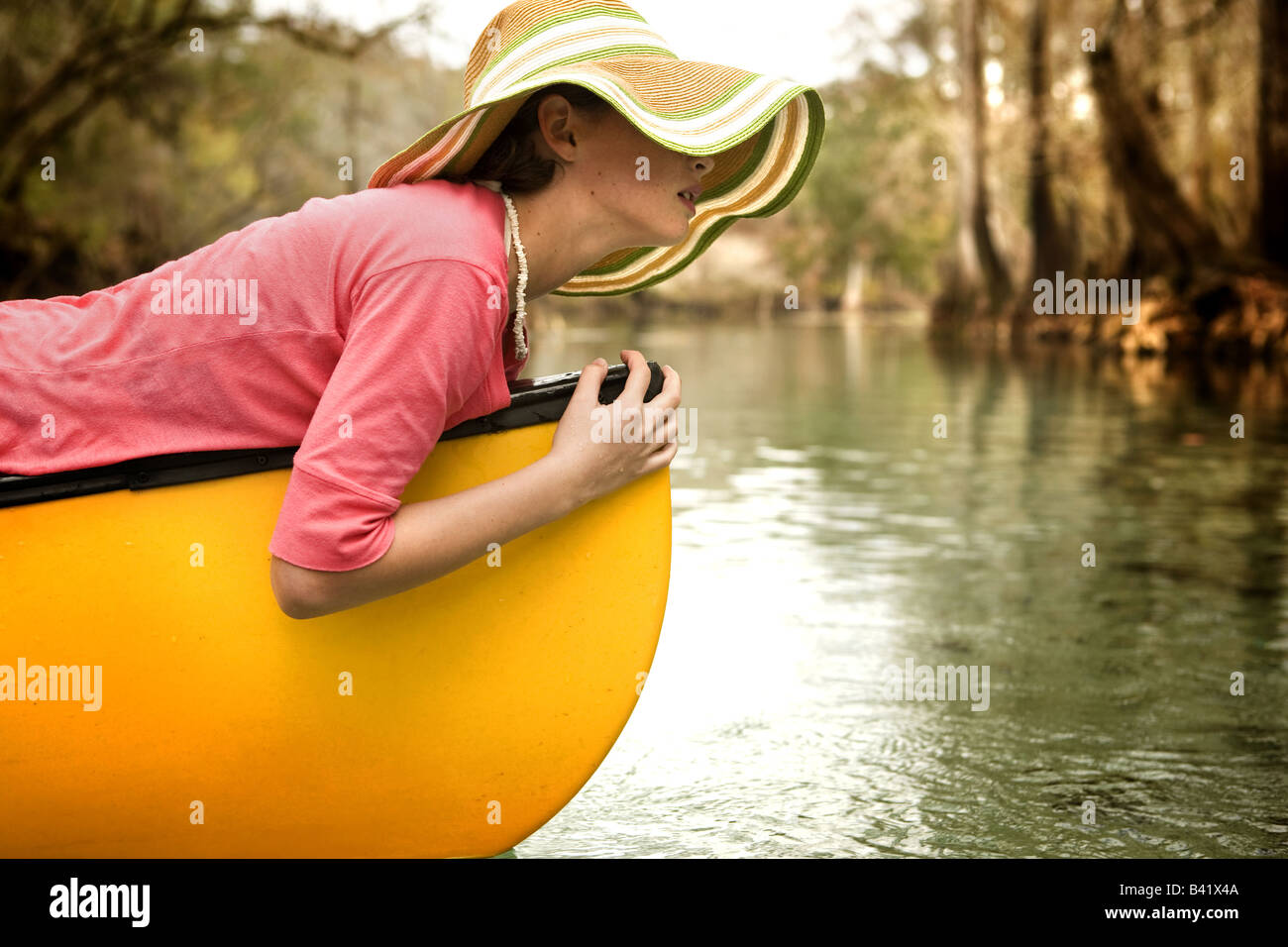 A young girl relaxes on her canoe in the clear water, cypress lined river of a fresh water spring in High Springs, - Stock Image