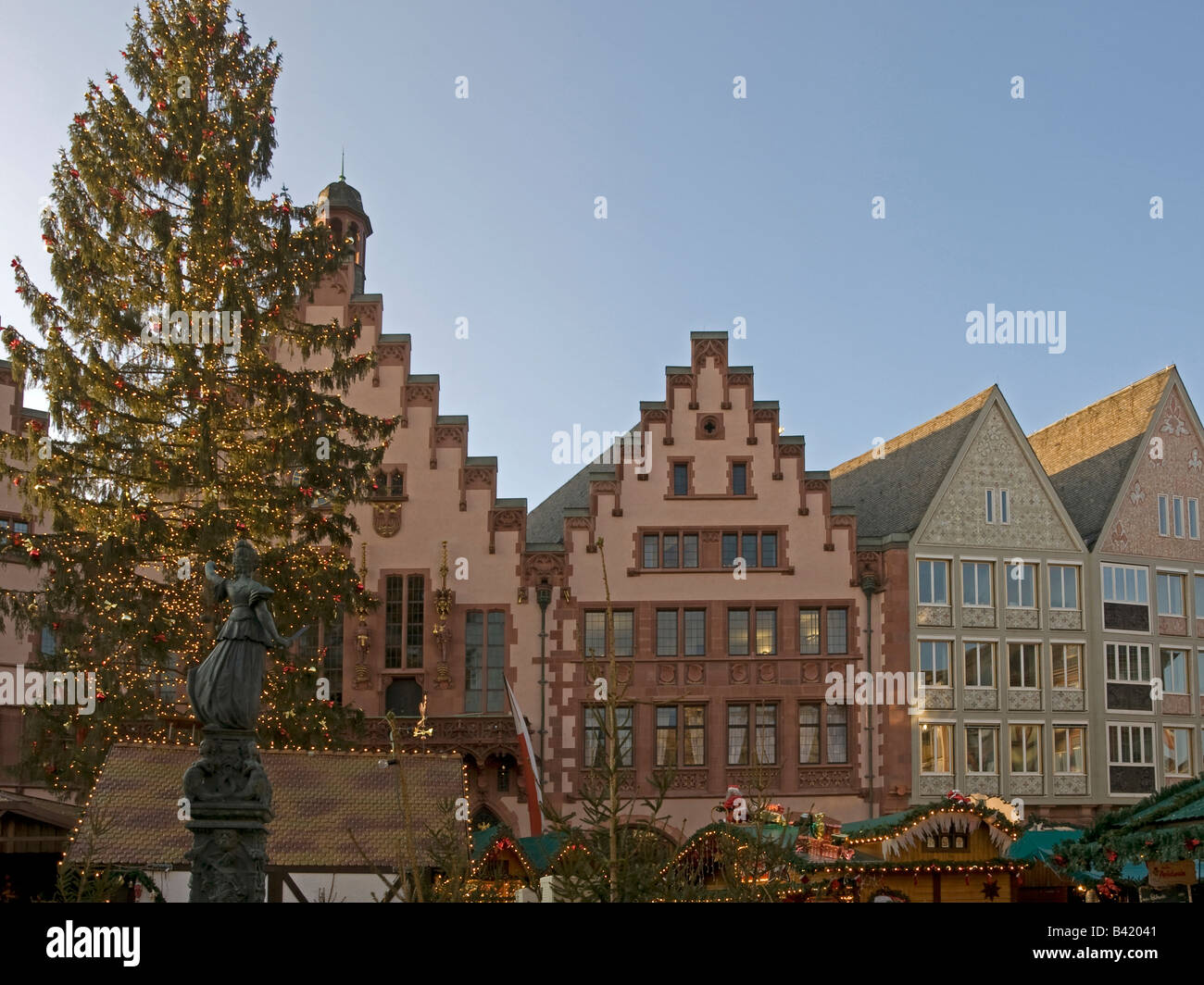 Christmas tree with fairy lights and boothes background city hall statue Justitia square Roemer Römer Römerberg - Stock Image