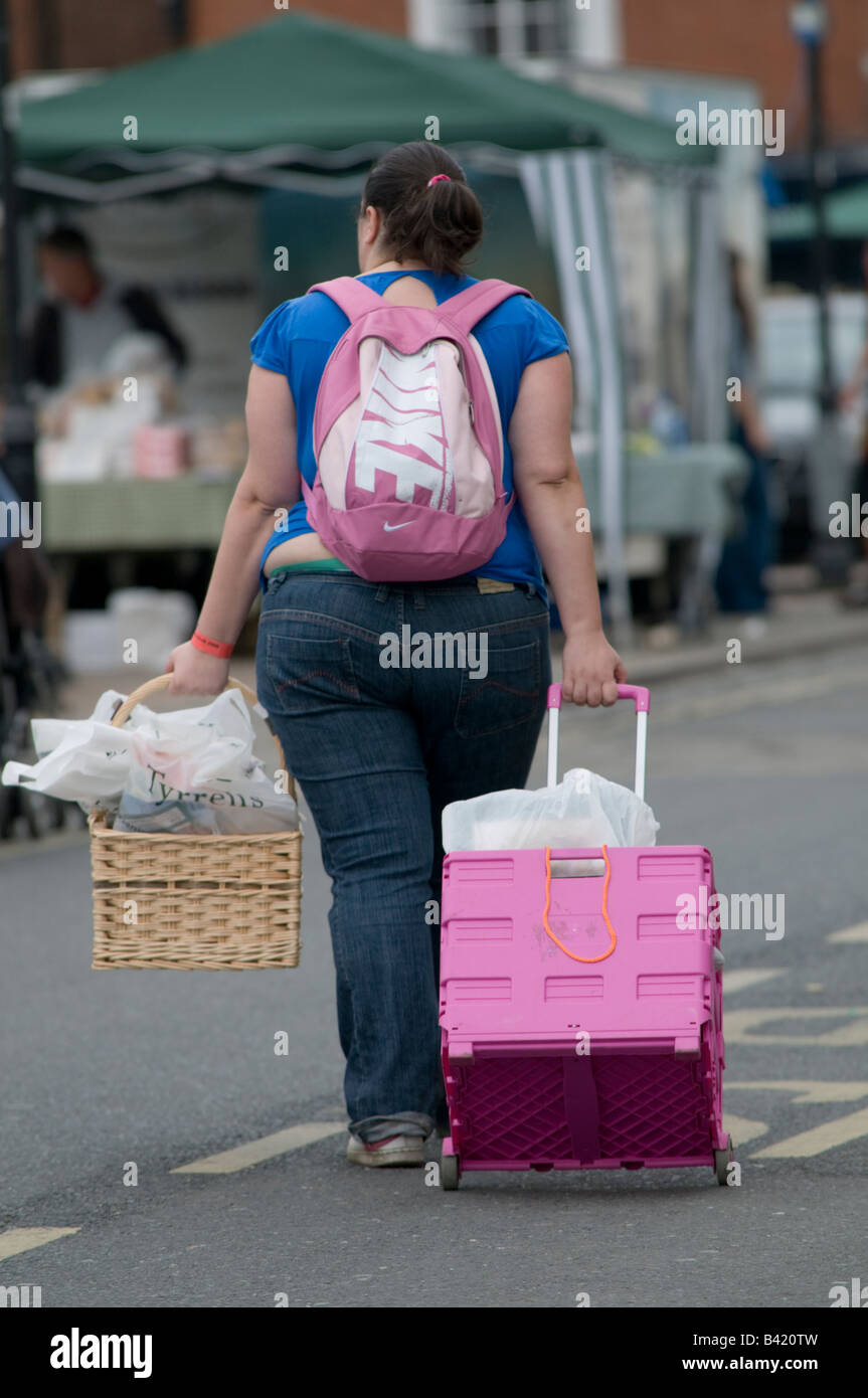 Young overweight woman walking with her shopping in a pink trolley in the street, Ludlow Shropshire UK - Stock Image