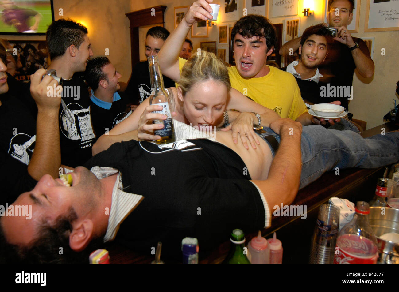 Young people playing drinking games in a bar. - Stock Image