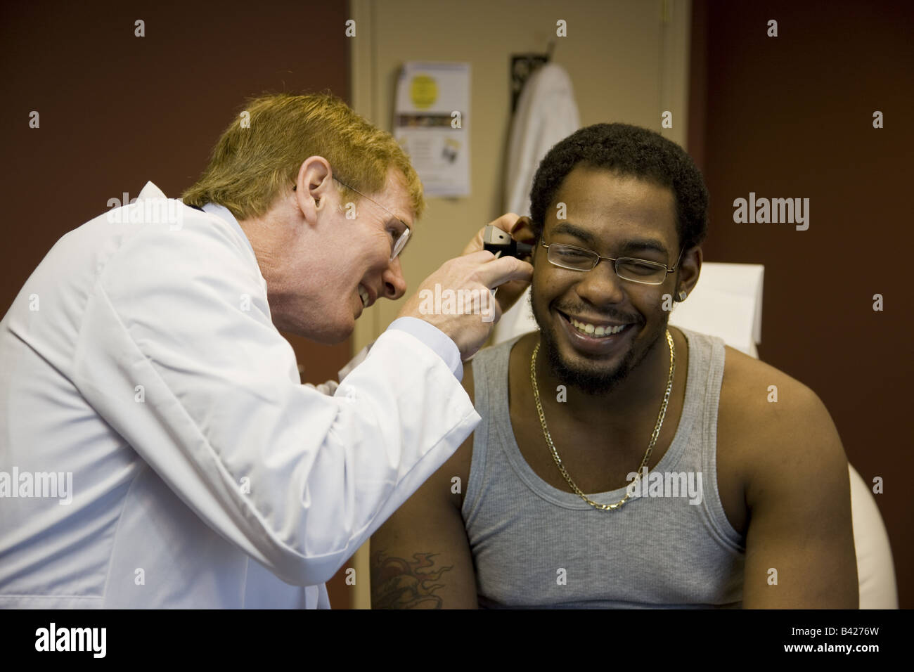 A doctor examines the ears of an African-American man during a physical examination. Stock Photo