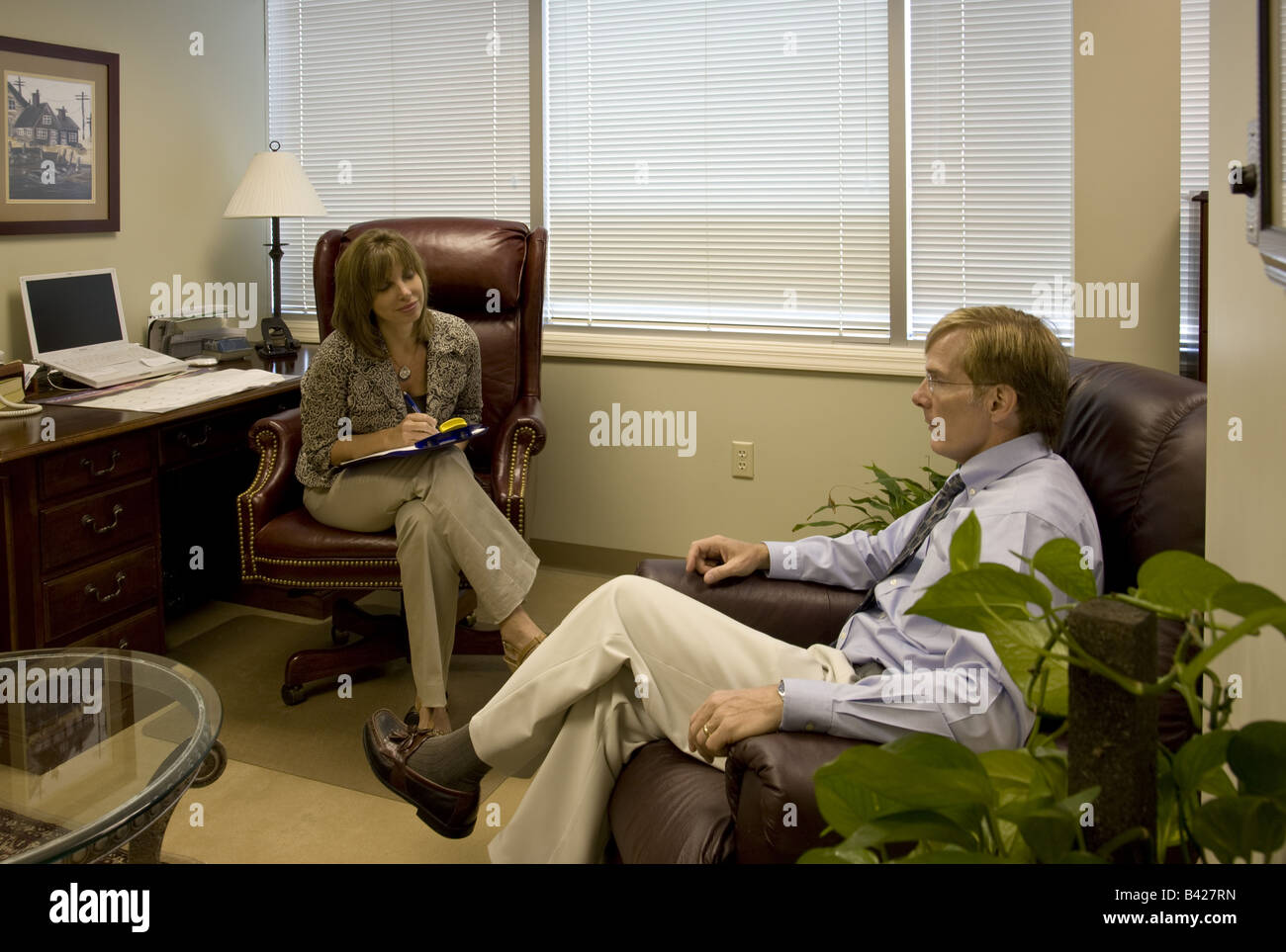 A female psychotherapist conducts a therapy session with a middle-aged man. Stock Photo