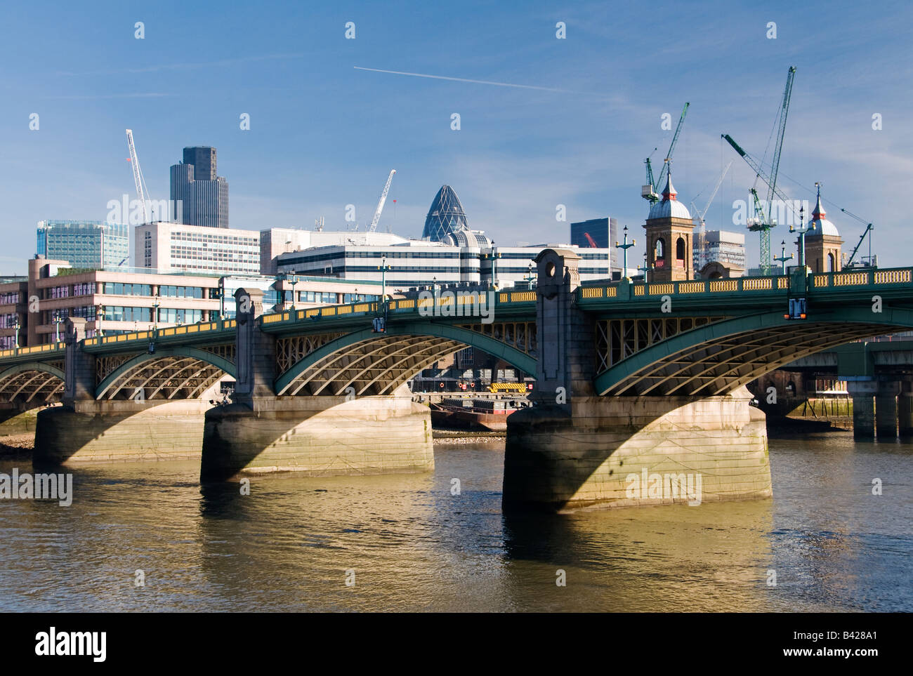 Southwark Bridge from the south bank of the Thames with Tower 42 and the Swiss Re Tower seen above the bridge, London, - Stock Image
