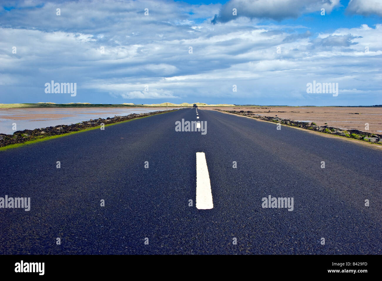 A long straight road stretching out on the Holy Island causeway Northumberland Great Britain UK 2008 Stock Photo