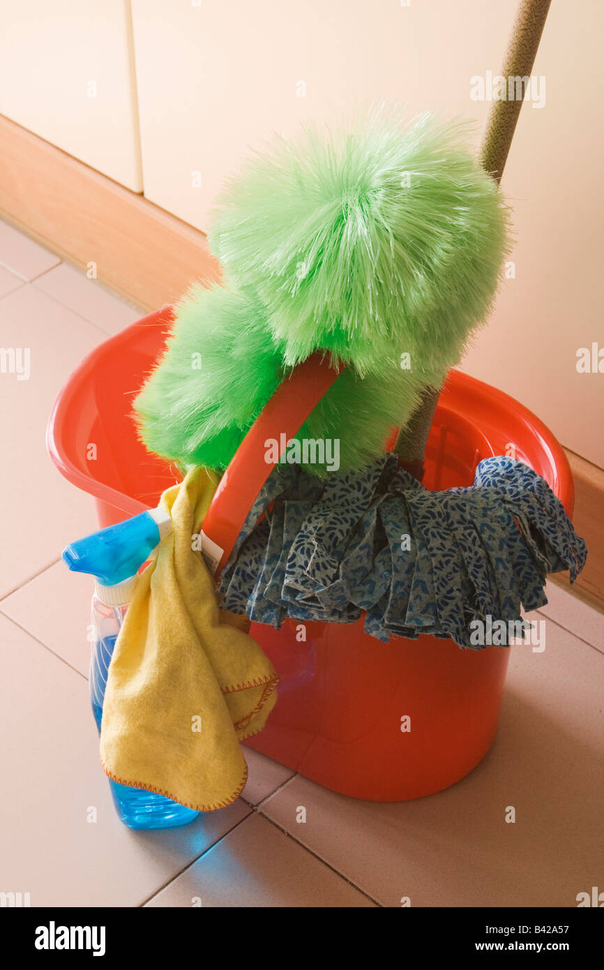 Red mop bucket mop green feather duster yellow duster blue cleaning fluid Stock Photo
