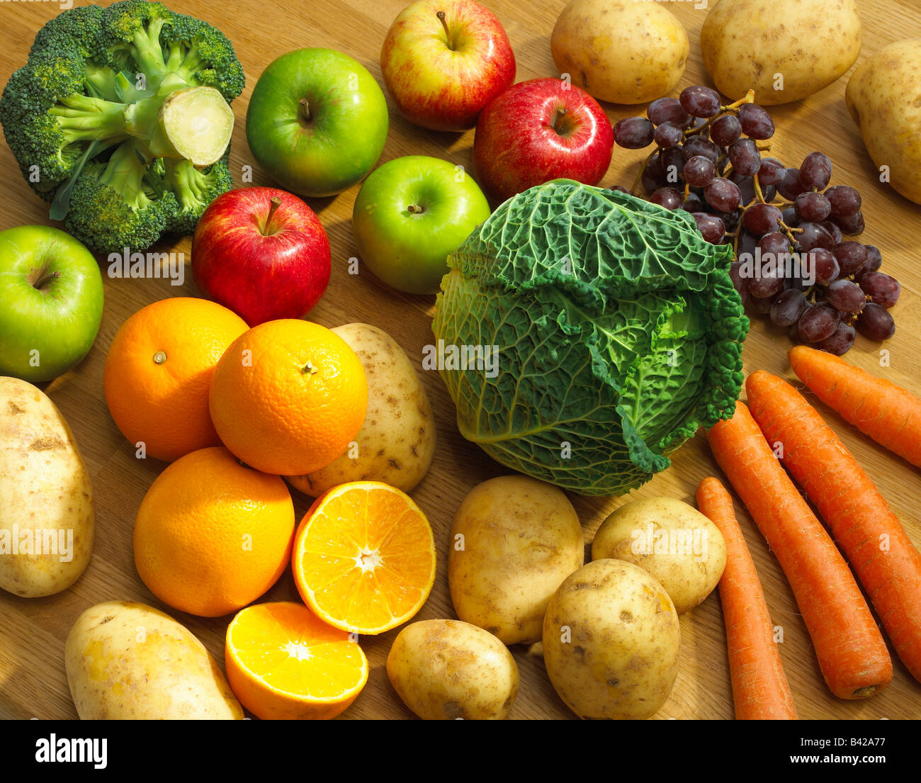 SELECTION OF FRESH FRUIT AND VEGETABLES WITH APPLES ORANGES GRAPES POTATOES CARROTS BROCOLLI AND CABBAGE - Stock Image