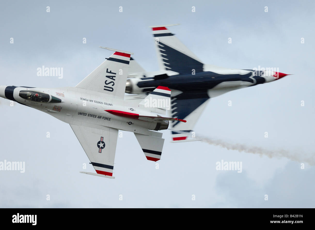 2 solos F-16 jet fighters passing each other - aerobatic team Thunderbirds in flight at Elmendorf Air Force Base - Stock Image