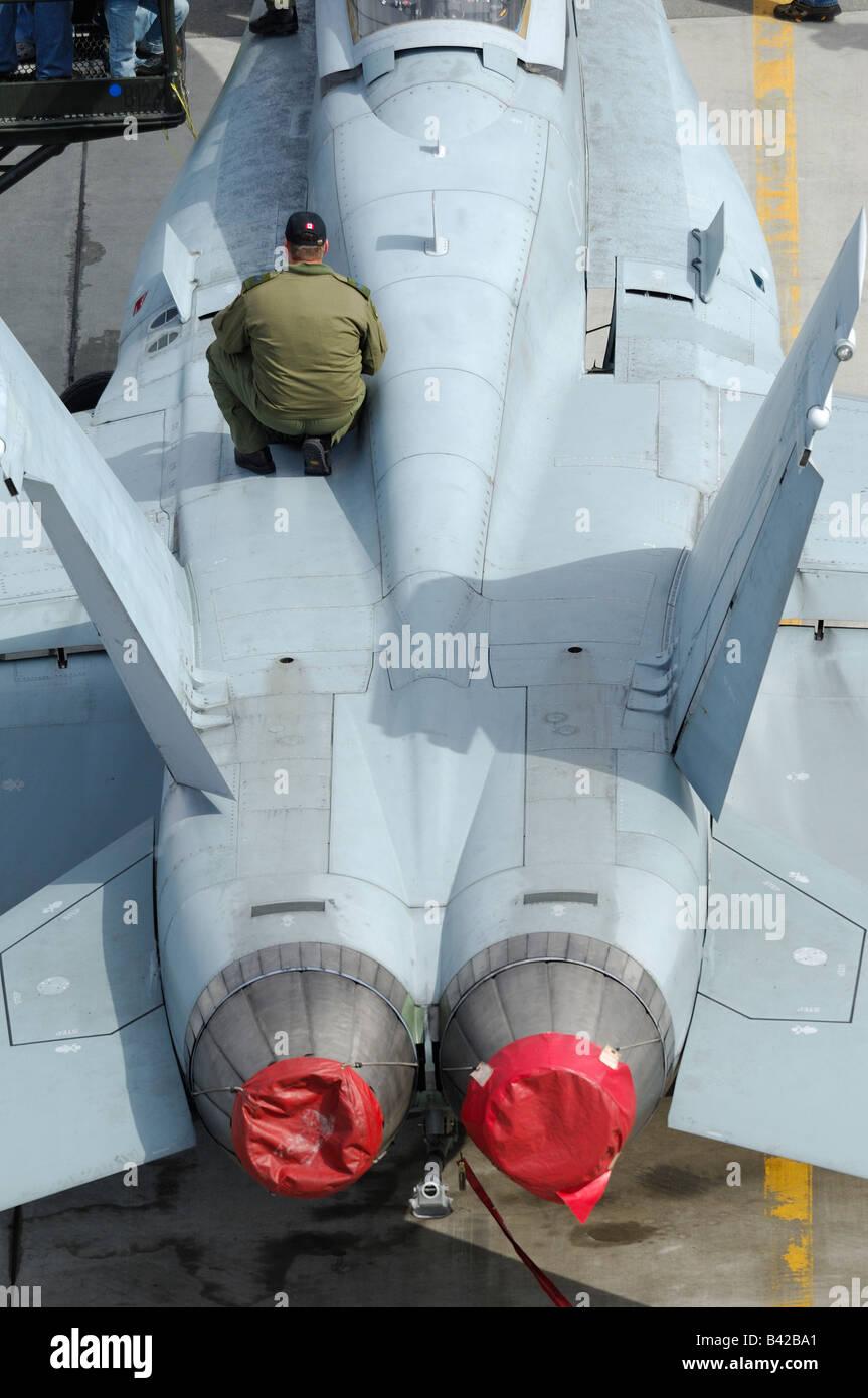 Mechanic inspecting fuselage of american jet fighter F-18 Hornet, Elmendorf Air Force base AFB, Anchorage, Alaska, - Stock Image