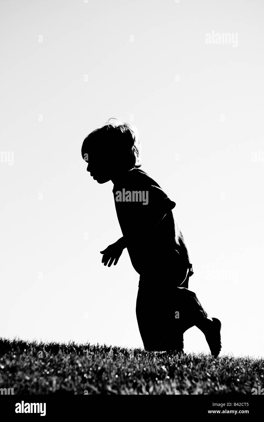 A silhouette of a barefoot boy running. - Stock Image
