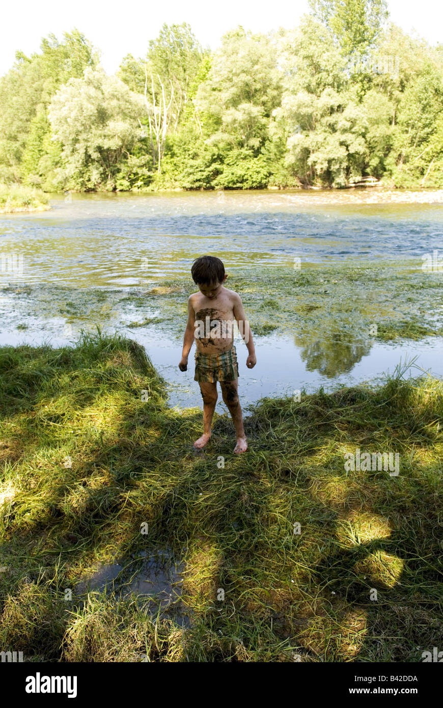 a young boy stands on a river bank looking down athis stomach covered in river mud and weed - Stock Image