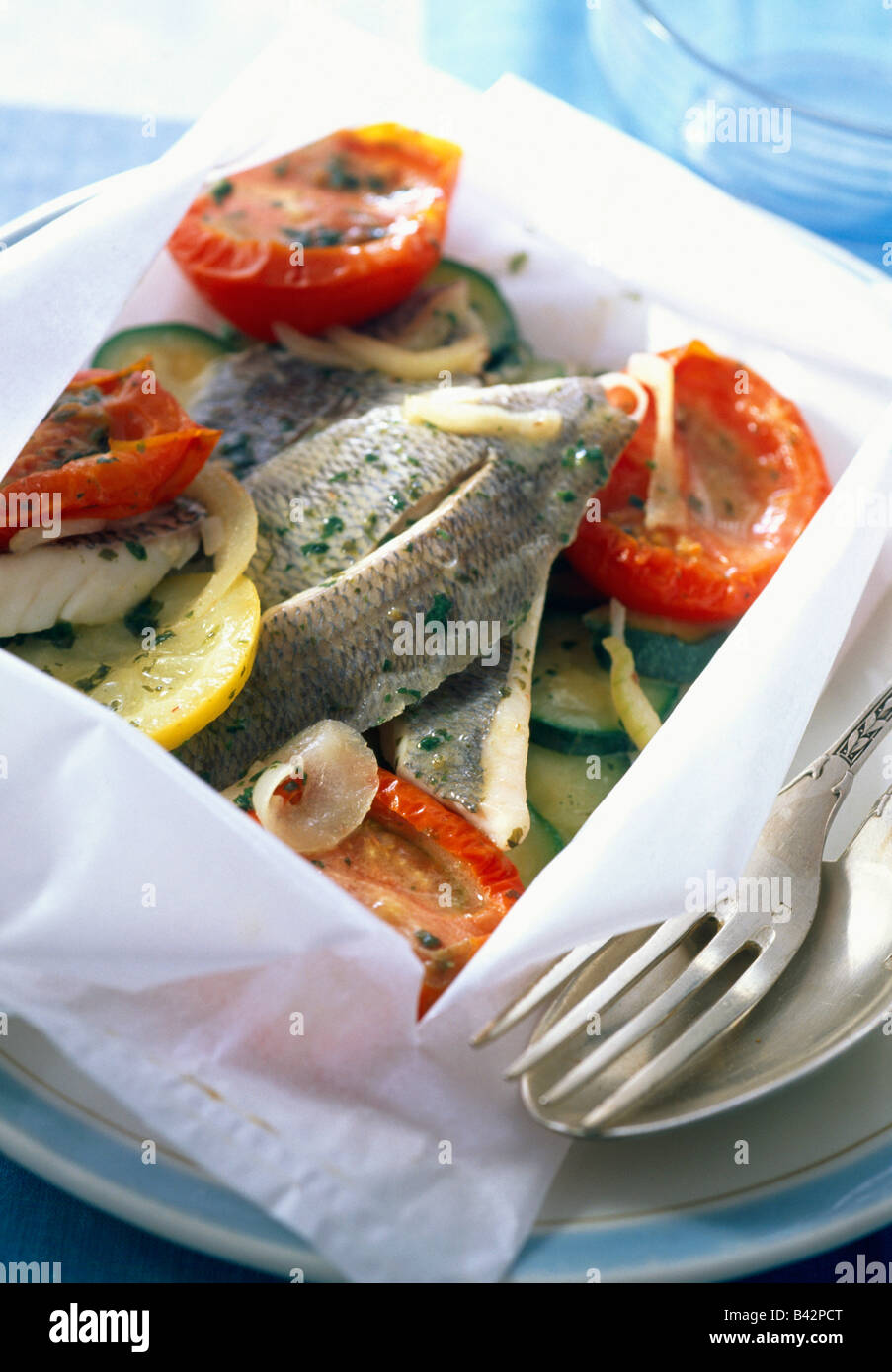 Sea bream fillets with preserved tomatoes and courgettes in papillote - Stock Image