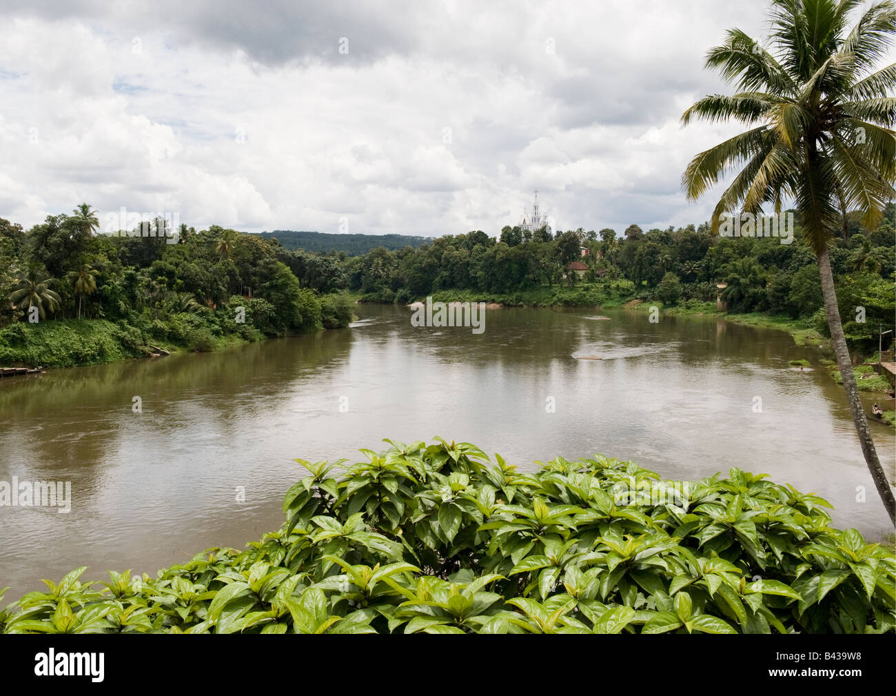 Periyar river flowing through lush green village farms with a momentous church in the background in this picturesque Stock Photo