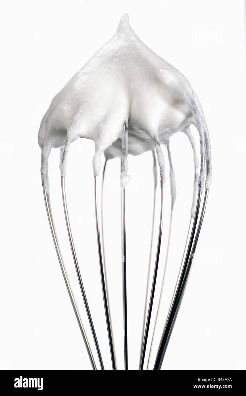 Egg whites on whisk - Stock Image