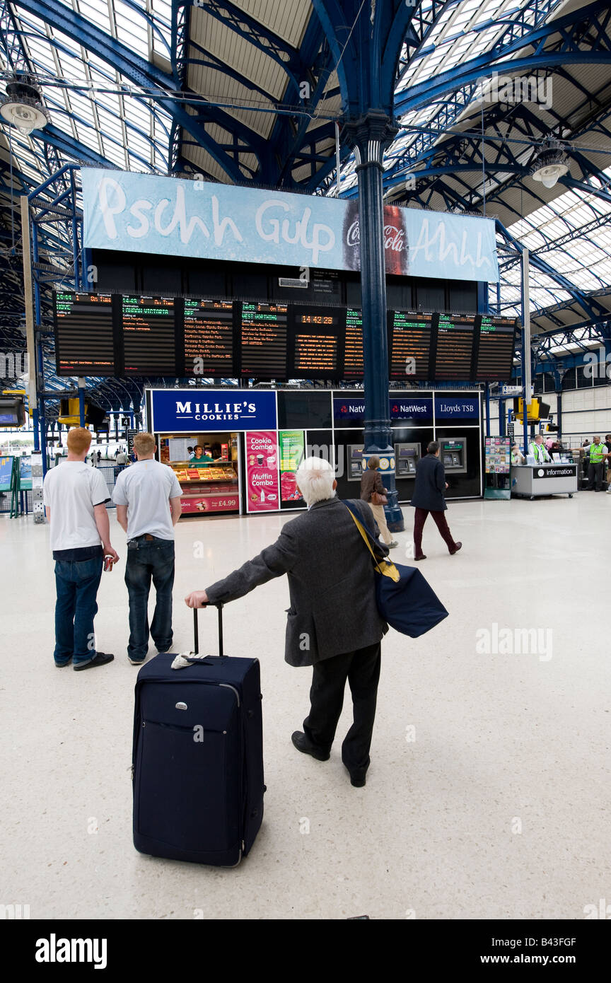 People waiting in front of the timetable information boards on the concourse area of brighton station east sussex Stock Photo