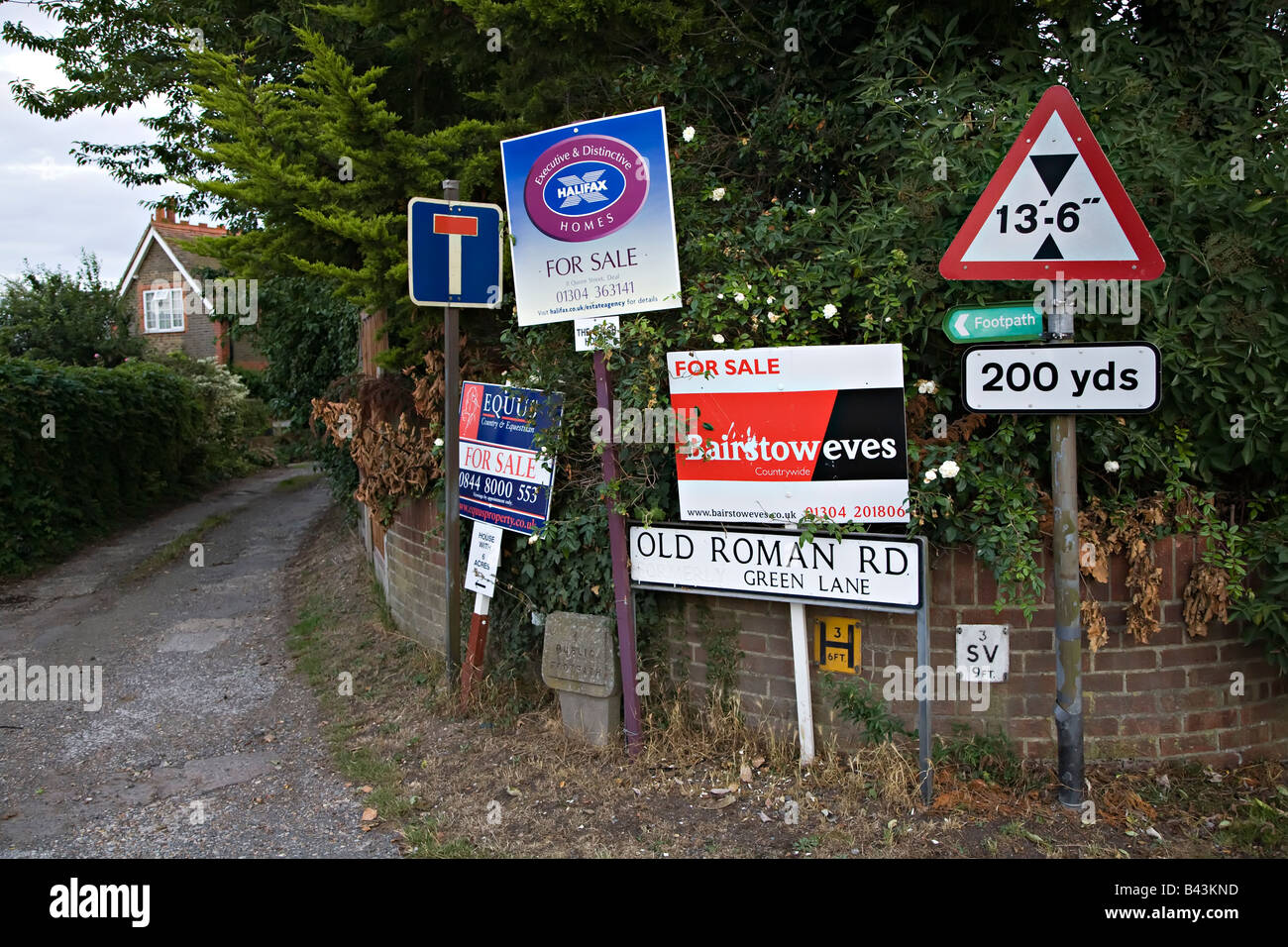 Houses for sale signs at end of road in village near Dover England UK - Stock Image